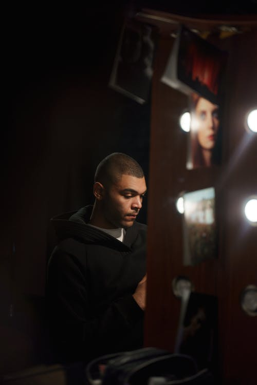 Man in Black Coat Sitting Infront Of A Mirror