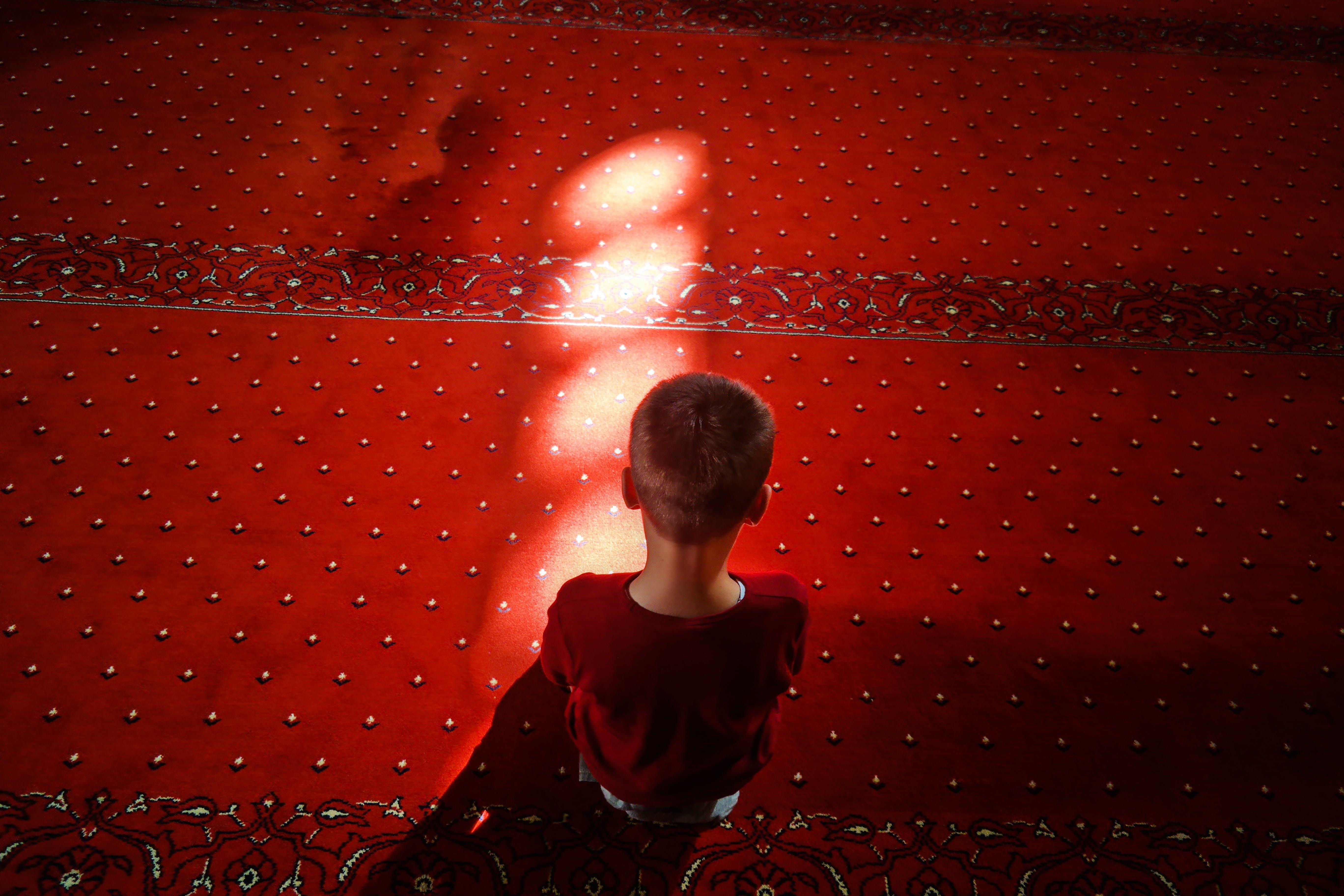 Child Sitting on Red Carpet