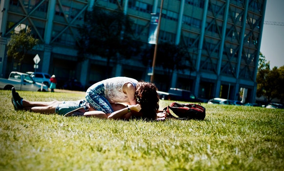 Man and Woman Lying on Green Field