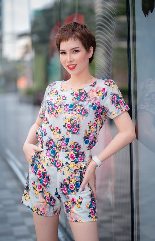 Woman in White Red and Blue Floral Outfit Standing Beside Glass Window
