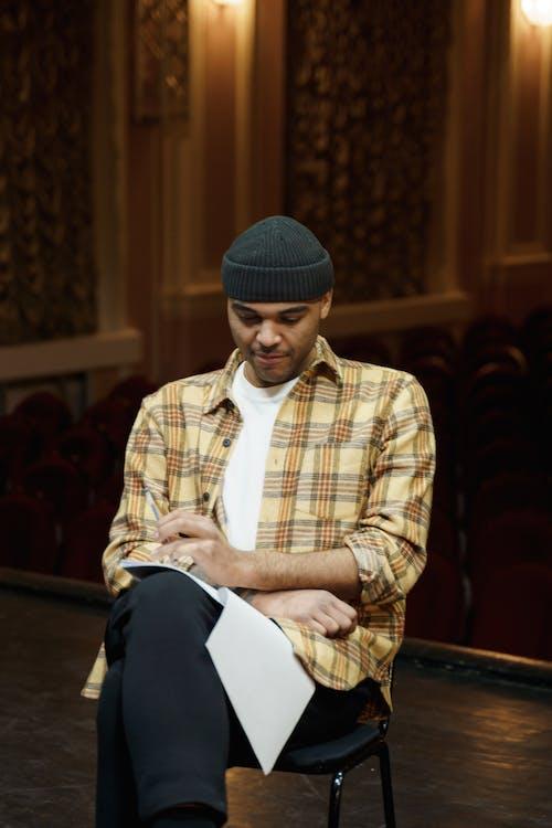 Man in Plaid Shirt Reviewing His Script