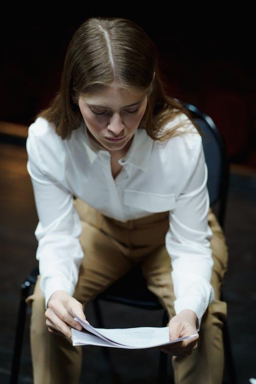 Woman in White Dress Shirt Reading A Script