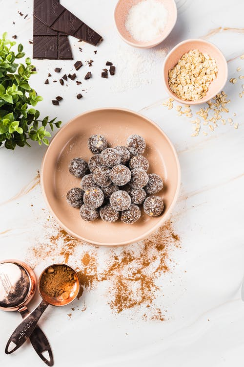Top view of delicious chocolate candies with coconut flakes in bowl near spoons with cacao powder and plant next to bowl with sugar and oatmeal on table