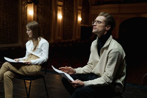 Man And Woman Sitting With Their Scripts