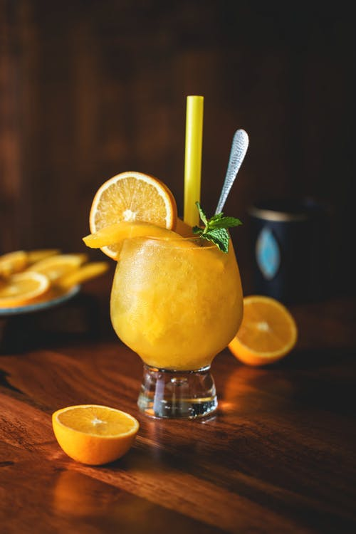 Glass with refreshing alcohol cocktail decorated with slice of orange and mint with straw near fruits on table