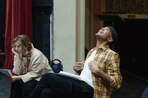 Man Laughing Beside A Woman Studying