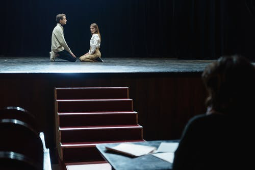 Man Watching Two People On Stage