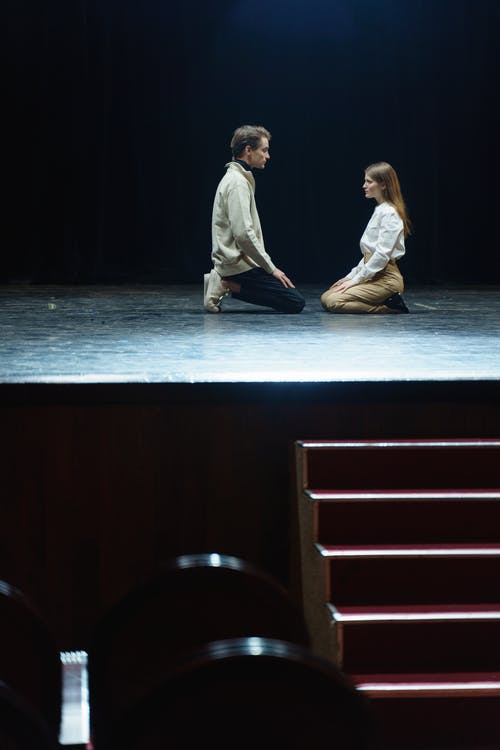 Man And Woman On Stage In A Kneeling Position