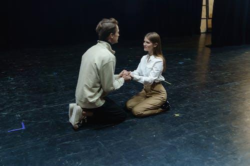 Man Kneeling In Front Of A Woman Sitting On Floor