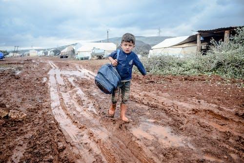 Full body of poor boy in rubber boots walking wth heavy backpack in small settlement