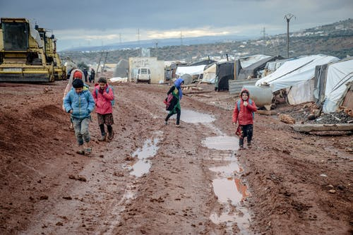 Poor children walking on muddy ground in settlement with tents