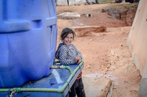 Happy poor girl near huge reservoir with water