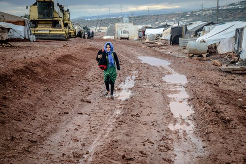Full body of islamic girl in shabby clothes strolling in brown mud near gray tents of rural settlement