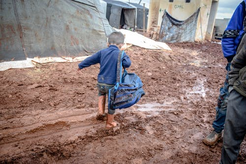 Boy with dirty legs and backpack strolling in village
