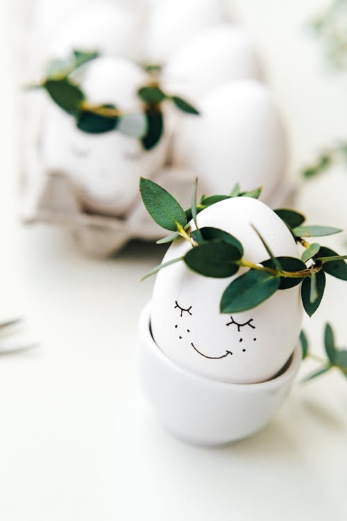 White Painted Eggs With Crown Of Green Leaves