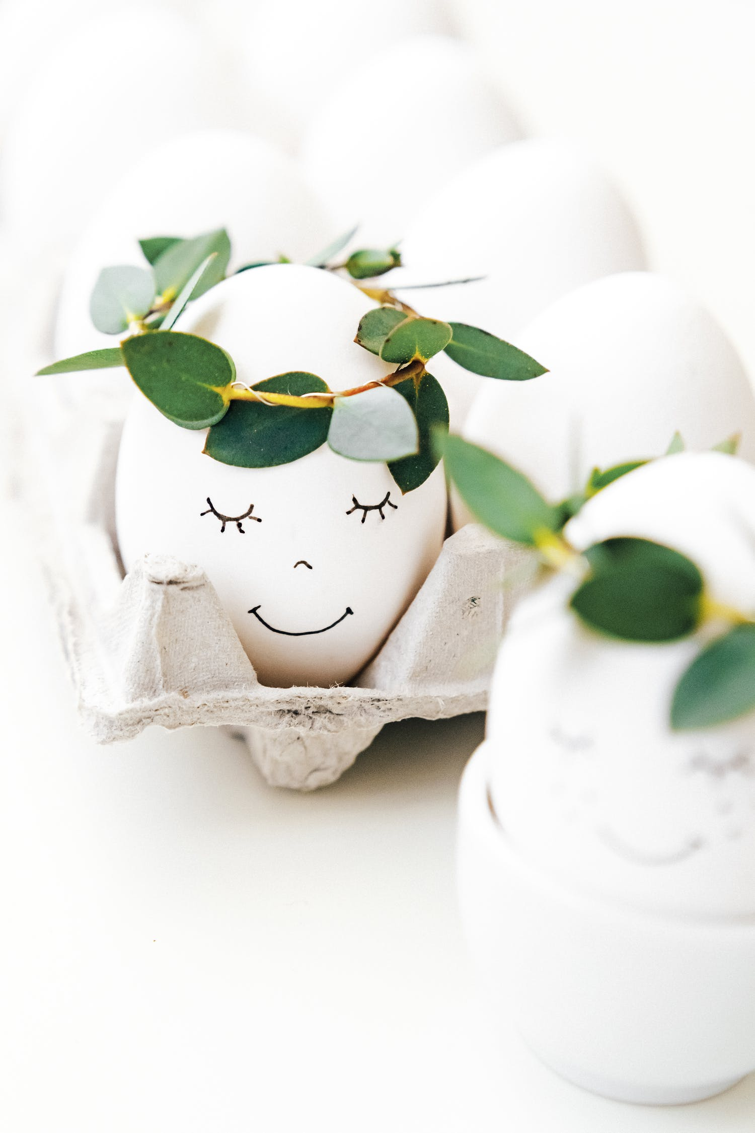 White Egg With Painted Face And Crown Of egLeaves