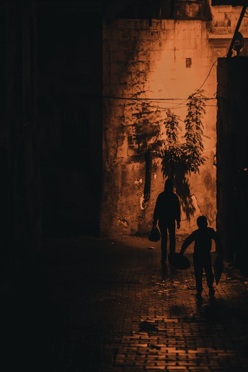 Silhouette of 2 Person Walking on Hallway