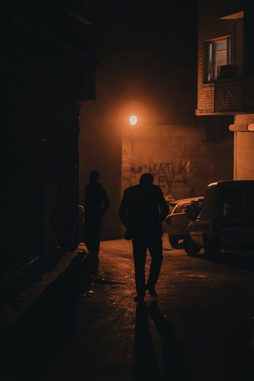 Man in Black Jacket Walking on Sidewalk during Night Time