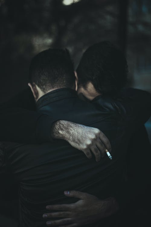 Anonymous grieving male friends in formal black suits embracing while comforting each other on street against blurred background