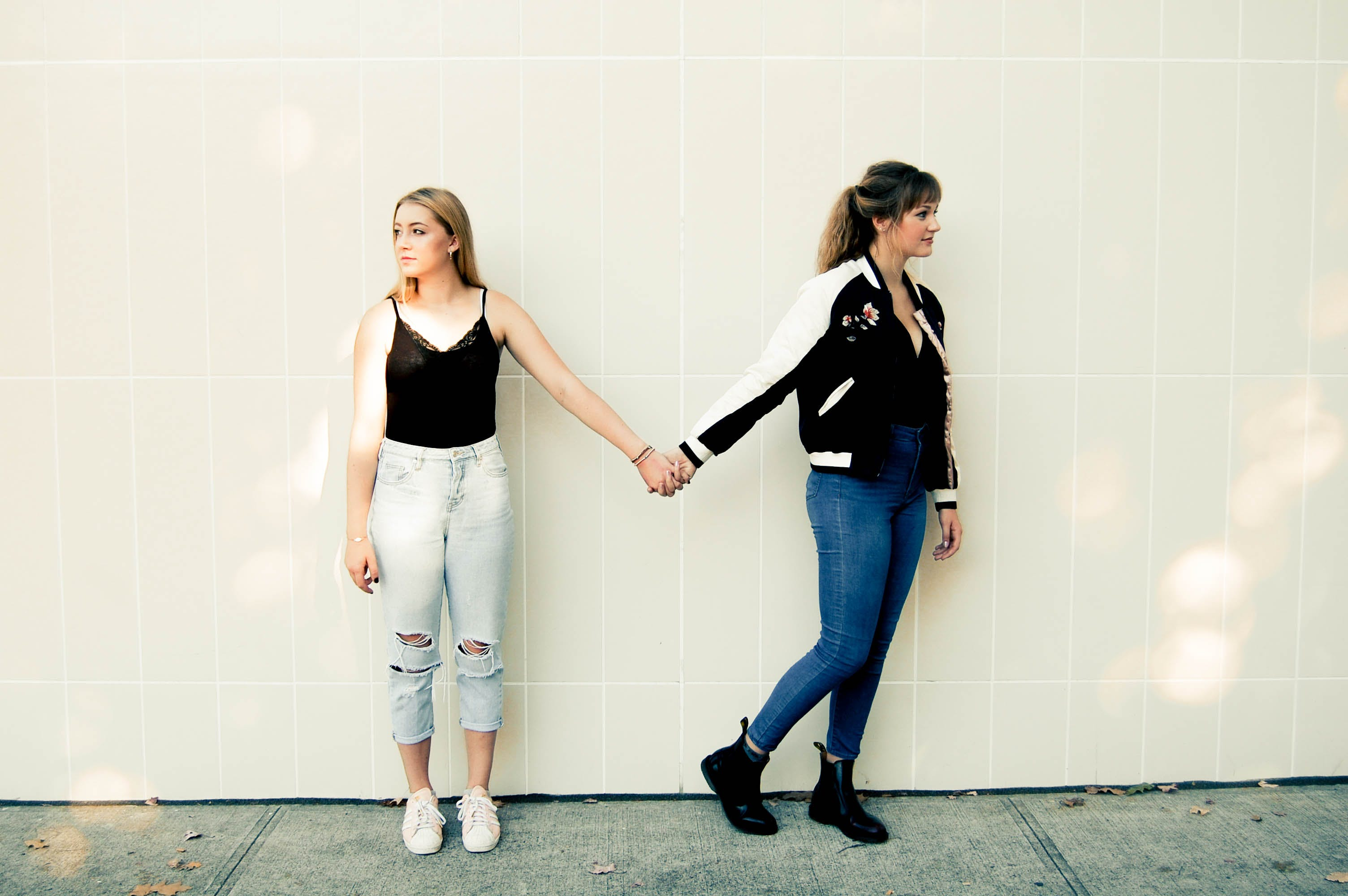 Two Women Standing Against Wall