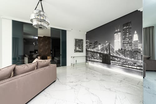 Mirror reflection of modern house with couch with pillows under chandelier near glass door and city wall mural
