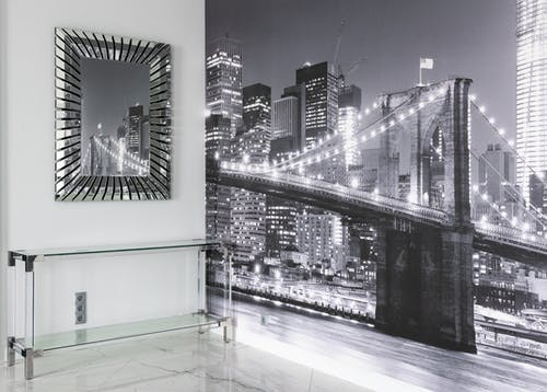 Interior of light modern flat with city wall mural next to glass table under mirror