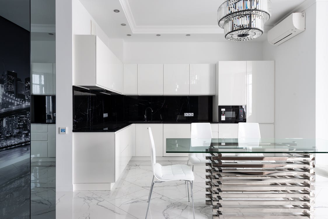Interior of light modern studio with glass table near chairs under chandelier next to open kitchen with white cabinets