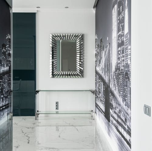 Interior of contemporary house with mirror above glass table next to city wall mural