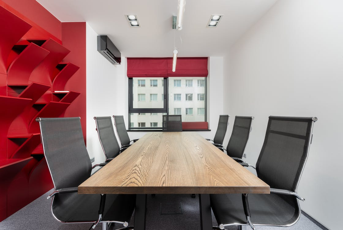 Interior of modern conference room with wooden table and chairs next to red shelves near window with jalousie