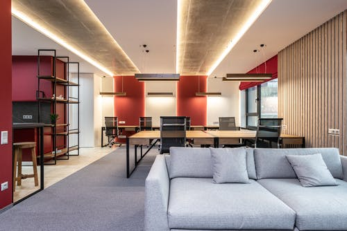 Lounge zone in office with couch near tables with chairs
