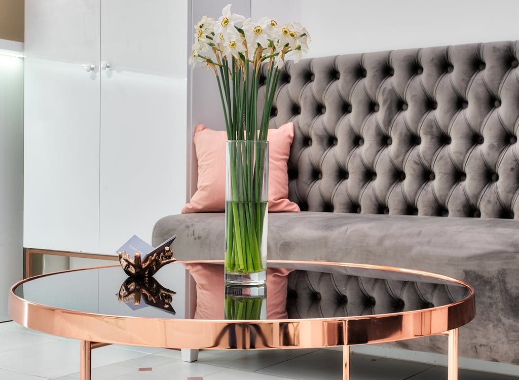 Blooming Narcissus bouquet in vase against couch in modern lobby