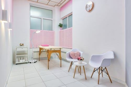 Interior of beauty salon with table for spa procedures and set of skincare products and flower decorations