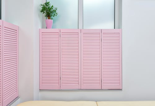 Minimalist interior of beauty office with couch for clients and pink shutters covering window