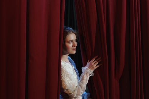 Woman in White Floral Lace Dress Standing Behind a Curtain