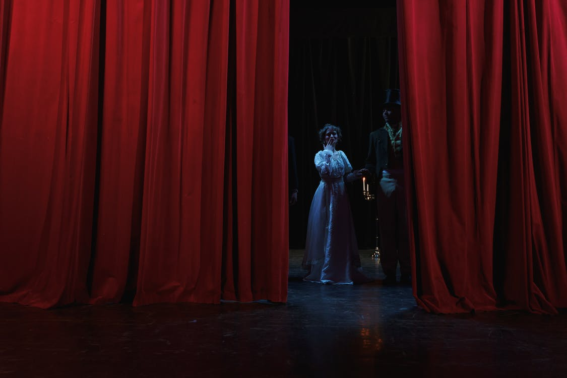Man And Woman Standing Behind A Red Curtain
