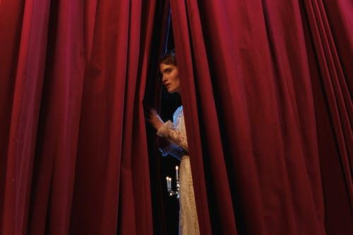 Woman Standing Behind Red Curtain