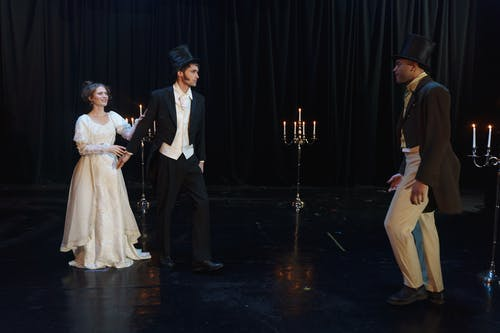 Three People Acting On Stage