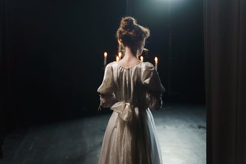Back View Of A Woman Holding A Candelabrum
