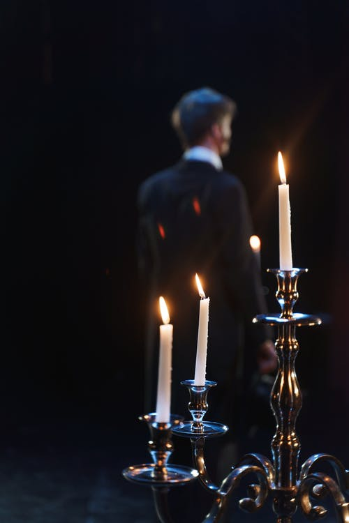 Blur Photo Of Man Standing Near A Candelabrum