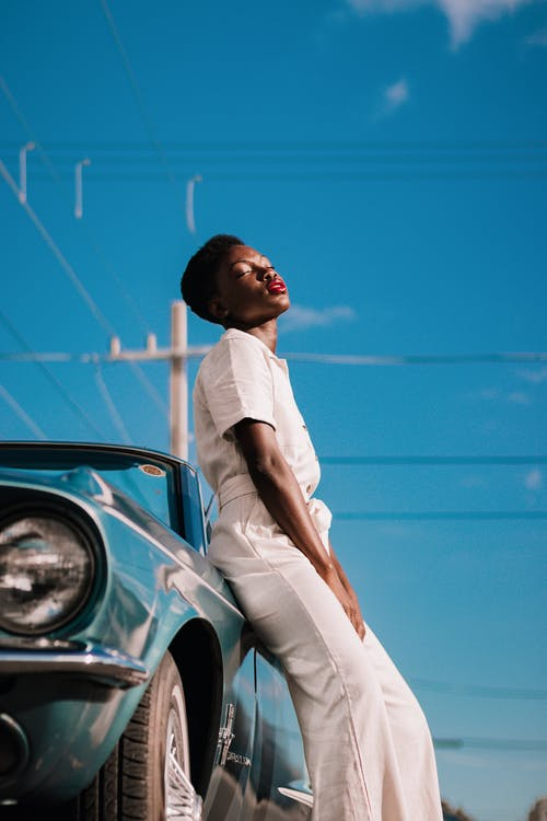 Side view of young African American female in stylish white outfit with closed eyes and bright red lips leaning on vintage car on blurred background of clear blue sky