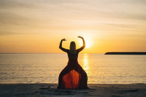 Woman in Orange Dress Standing on Beach during Sunset