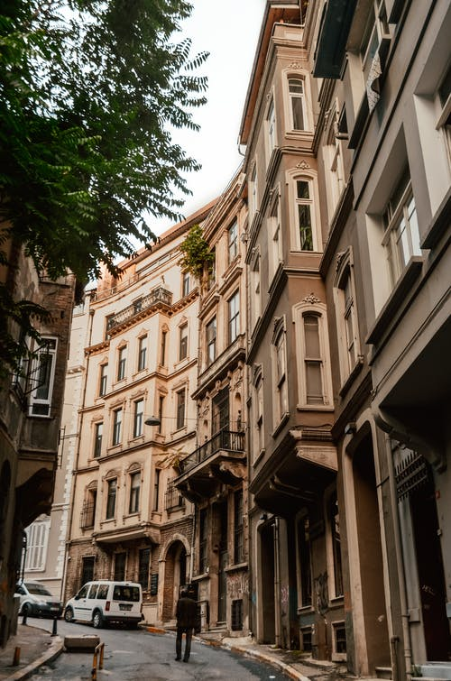From below of anonymous traveler walking along narrow street between aged residential buildings on sunny day in Istanbul
