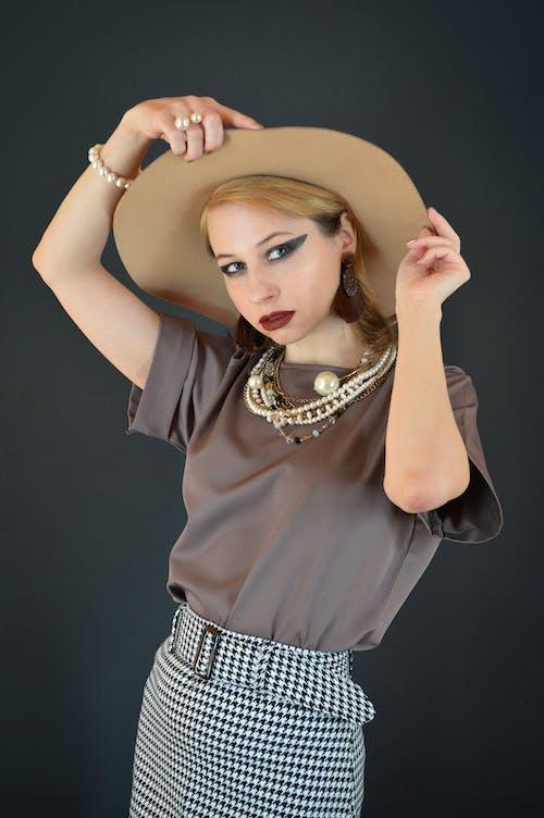 Stylish young female model adjusting hat in black studio