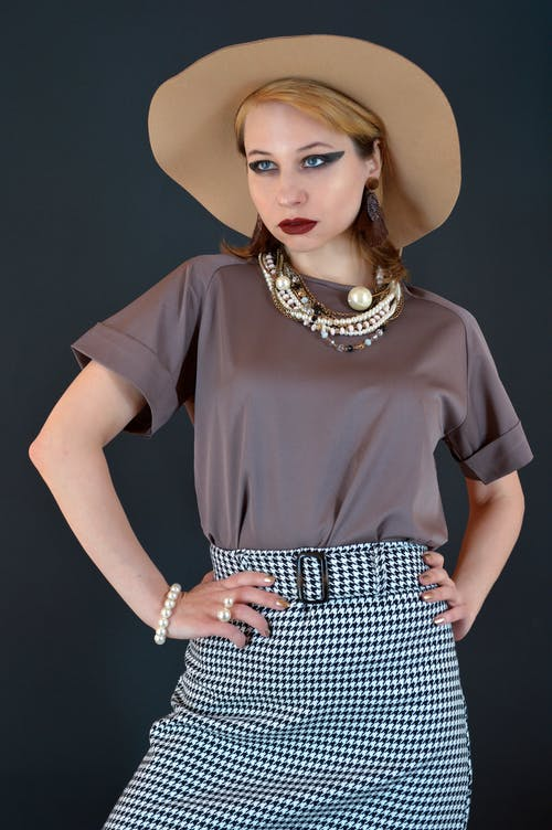 Self esteem young female model in stylish outfit and hat with bright makeup standing against black background with hands on waist and looking away