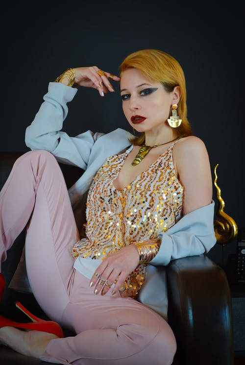 Confident female model wearing fashionable clothes sitting on couch and touching head while looking at camera
