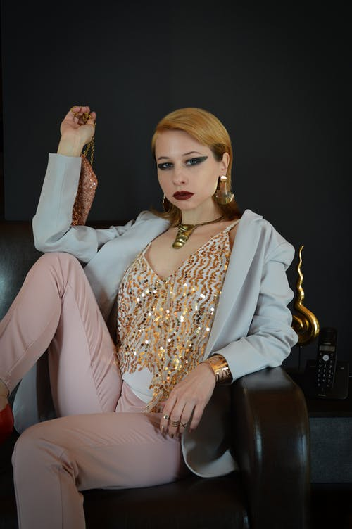 Serious female model in fancy outfit and accessories sitting on sofa with handbag and looking at camera