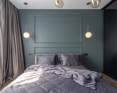 Stylish bedroom with unmade bed near window with curtains