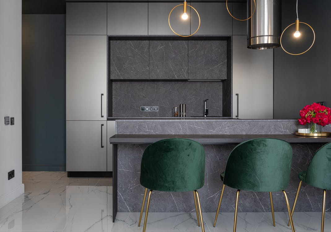 Interior of modern kitchen furnished with armchairs near counter decorated with vase of flowers and gray cupboards