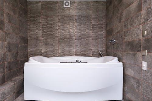Modern bathtub in bathroom with tiled walls