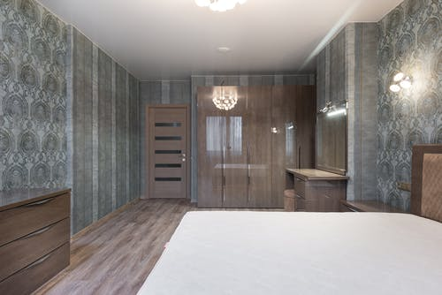 Interior of new bedroom with bed and wooden furniture
